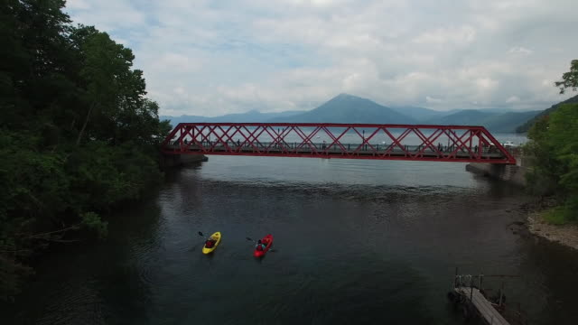Aerial Shot: Drone: Bird's-eye view of two kayaks (one red, the other yellow) on the Chitose River