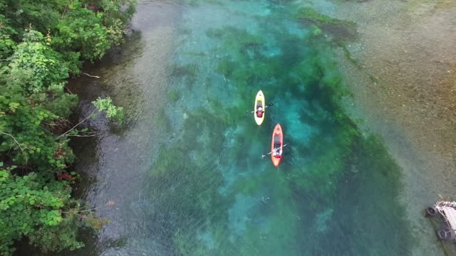 aerial shot: drone: bird's-eye view of two kayaks (one red, the other yellow) on the chitose river - pedal boat stock videos and b-roll footage