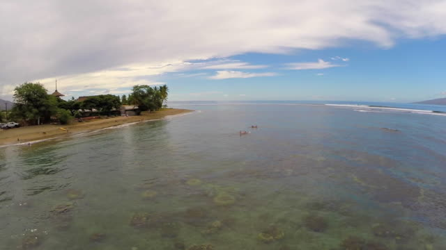 aerial shot flying backwards over calm ocean inlet with in maui, hi - andersherum stock-videos und b-roll-filmmaterial