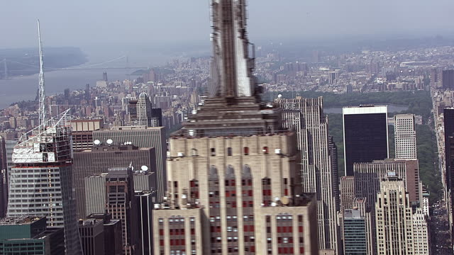 aerial shot flying by the empire state building with central park in the background in manhattan, new york city. - 2010 stock videos & royalty-free footage