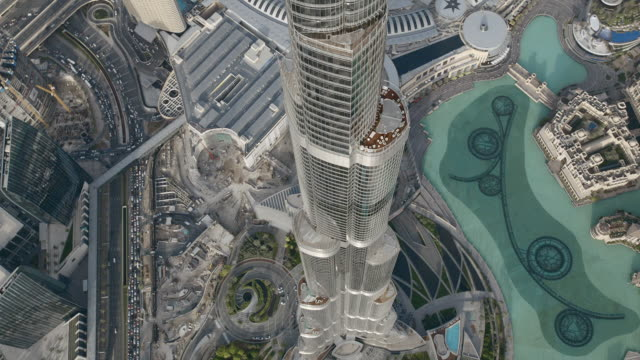 Aerial shot flying down along the shimmering facade of the Burj Khalifa in Dubai. The skyscraper is currently the tallest in the world.