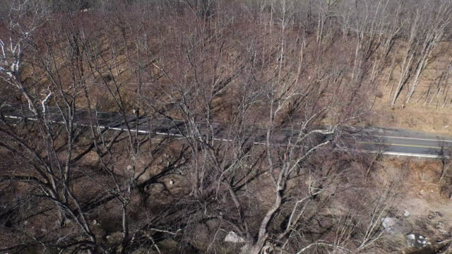 aerial shot flying next to trees, looking at a road with cars, and river in the winter - new paltz stock videos and b-roll footage