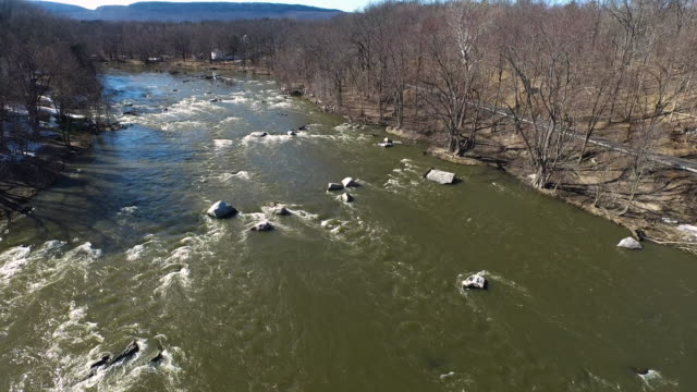 aerial shot flying over a river, looking at a road with cars, and trees in the winter - new paltz stock videos and b-roll footage
