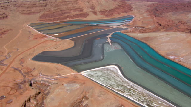 stockvideo's en b-roll-footage met aerial shot flying over colorful evaporation ponds at a potash mine near moab, utah. - moab utah
