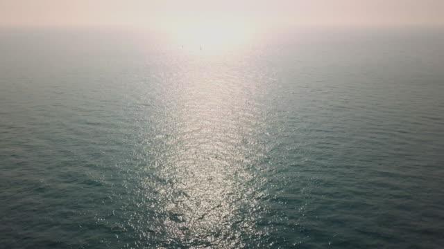 vídeos de stock, filmes e b-roll de aerial shot 4k: flying over deep blue ocean - baixo posição