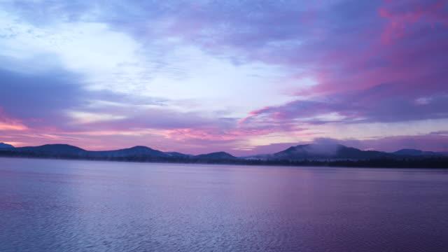 vidéos et rushes de aerial shot flying over lake at sunrise, adirondacks ny - violet