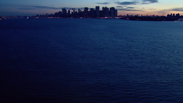 Aerial shot flying over New York Harbor at dawn, tilting up to reveal Lower Manhattan.