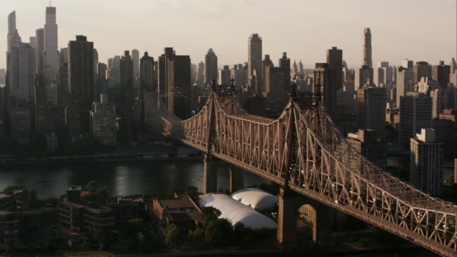 aerial shot flying over queensboro bridge and roosevelt island at the end of the day, nyc - queensboro bridge stock videos & royalty-free footage