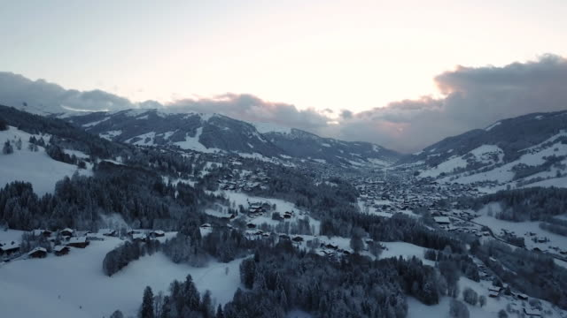 Aerial shot flying over snow covered mountains at sunset