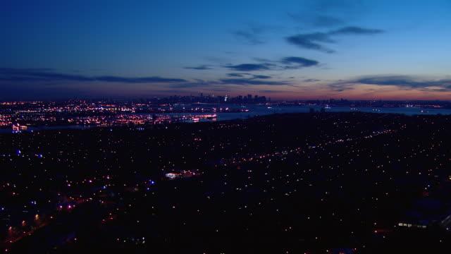 Aerial shot flying over Staten Island towards Lower Manhattan at dawn.