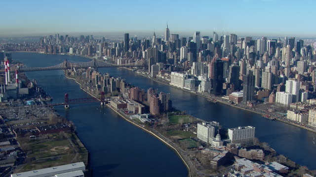 aerial shot flying over the east river and roosevelt island toward the skyscrapers of manhattan's upper east side and midtown in new york city. - cantilever bridge stock videos & royalty-free footage