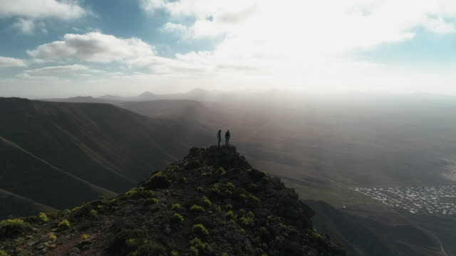 vidéos et rushes de aerial shot flying over two backpackers at the edge on a mountain ridge, lanzarote, spain - spain