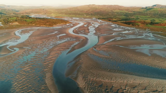 aerial shot flying towards an estuary at low tide during sunset, borth-y-gest, wales, united kingdom - low tide stock videos & royalty-free footage