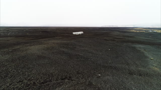 aerial shot flying towards and over the top of a plane wreckage on a black sand beach, iceland - 地形点の映像素材/bロール