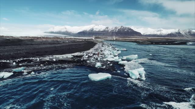 aerial shot flying towards diamond beach, jokulsarlon, iceland - natural condition stock videos & royalty-free footage