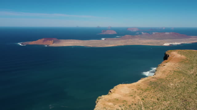 aerial shot flying towards the island of la graciosa from lanzarote, spain - cliff点の映像素材/bロール