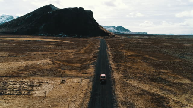 vídeos de stock, filmes e b-roll de aerial shot following a car driving along a dirt road in an icelandic landscape, iceland - rocha