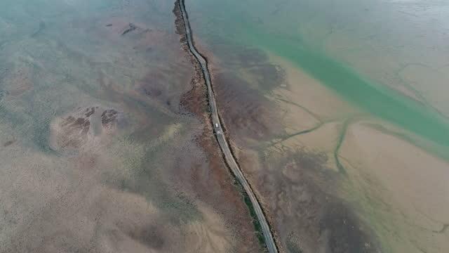aerial shot following a van crossing the osea island causeway at low tide, england, united kingdom - 囲む点の映像素材/bロール