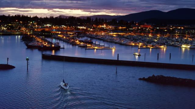 aerial shot following small sailboat into anacortes marina at nightfall - anacortes stock videos & royalty-free footage