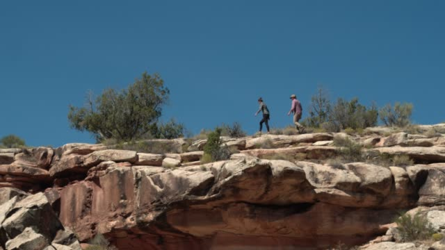 aerial shot from below of two people walking on a rocky rim of the colorado national monument in the desert of grand junction, colorado - rock face stock videos & royalty-free footage