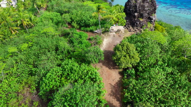 vidéos et rushes de aerial shot from the back of a young couple next to a ruin wall on a beautiful tropical island, drone flying forward while tilting down - bora bora, french polynesia - bora bora
