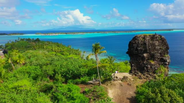 aerial shot from the back of a young couple sitting next to a ruin wall on a beautiful tropical island, drone ascending the flying backwards - bora bora, french polynesia - bak och fram bildbanksvideor och videomaterial från bakom kulisserna