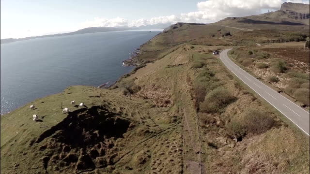 aerial shot from the isle of skye in scotland, revealing the coastline with small country road to the side and the old man of storr in the backgroun - hebriderna bildbanksvideor och videomaterial från bakom kulisserna