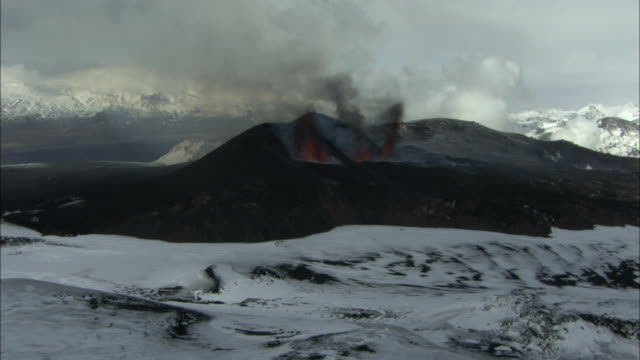 Aerial shot heading towards erupting volcano, snow on ground, Eyjafjallajokull, Iceland, April 2010