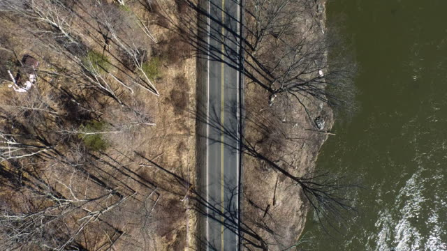 aerial shot looking directly down at trees, road, and river in the winter - new paltz stock videos and b-roll footage