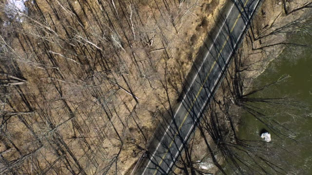 vídeos de stock, filmes e b-roll de aerial shot looking directly down at trees, road, and river in the winter - new paltz