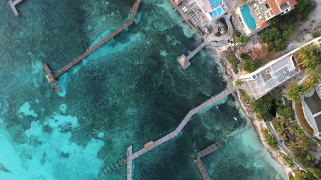 vídeos de stock, filmes e b-roll de aerial shot looking down at ocean, piers, and houses - quintana roo