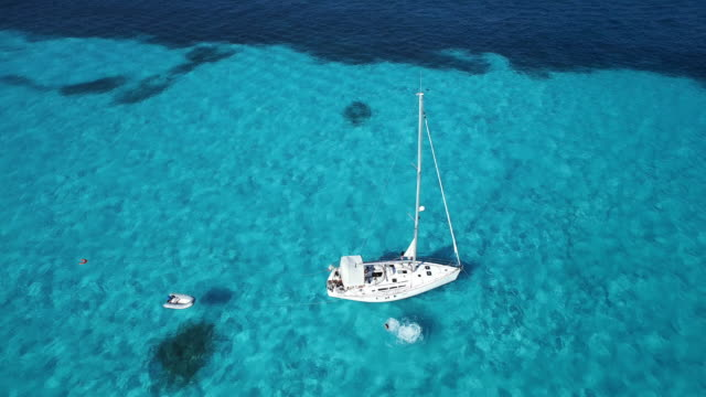 Aerial shot looking down at sailboat anchored in beautiful clear blue ocean