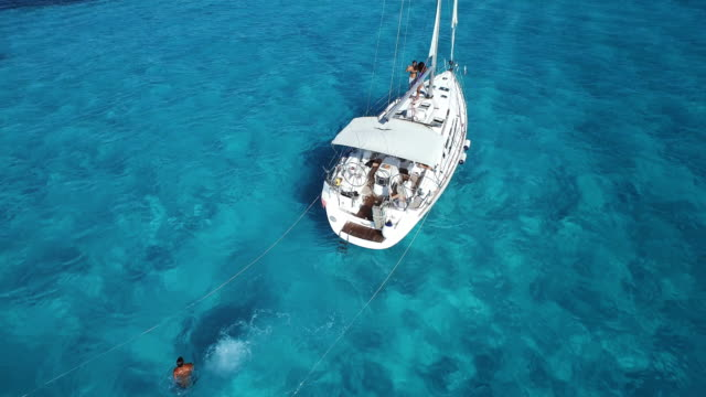 vídeos de stock, filmes e b-roll de aerial shot looking down at sailboat anchored in beautiful clear blue ocean - quintana roo