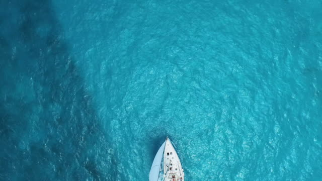 vidéos et rushes de aerial shot looking down at sailboat and beautiful clear blue ocean - voilier