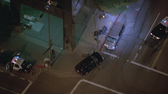 aerial. shot looking down from helicopter with spotlight on police scene. - arrest stock videos & royalty-free footage