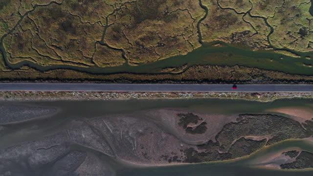 vídeos y material grabado en eventos de stock de aerial shot looking down on a car driving on a road crossing the marshlands, huelva, spain - marisma