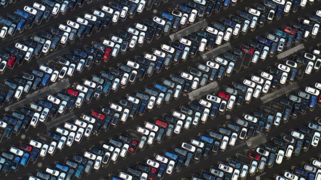 aerial shot looking down on a rows of vehicles at a car dealership, england, united kingdom - parken stock-videos und b-roll-filmmaterial