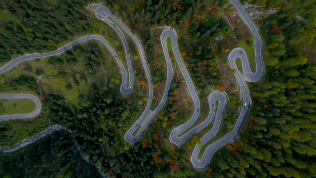 aerial shot looking down on cars driving along the maloja pass during autumn, switzerland - くねくねした点の映像素材/bロール
