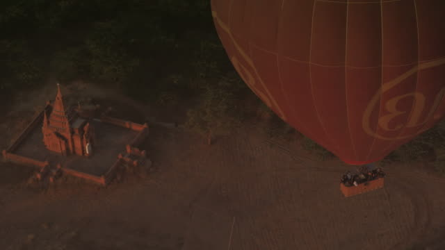 Aerial shot looking down on hot air balloon and temple at sunrise