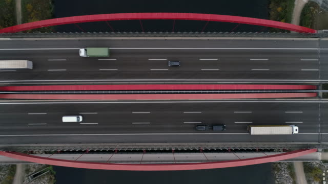 aerial shot looking down on traffic crossing a red coloured bridge, munich, germany - abstract stock videos & royalty-free footage
