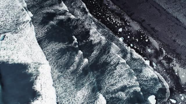 aerial shot looking down on waves washing ashore on diamond beach, jokulsarlon, iceland - abstract stock videos & royalty-free footage