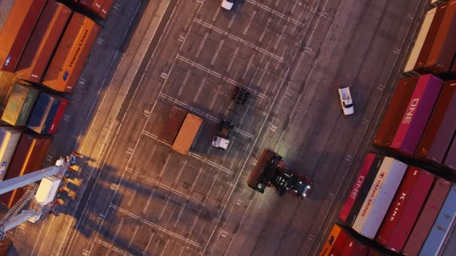 aerial shot looking straight down on top handler lifting shipping container at night - container stock videos & royalty-free footage