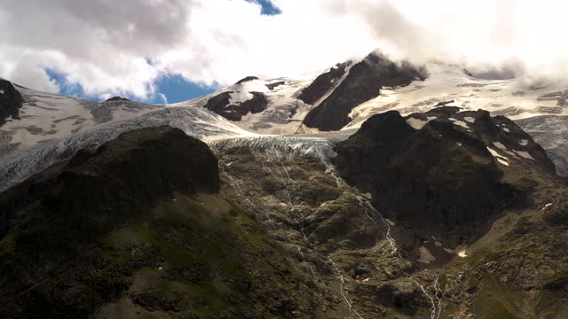 aerial shot looking up towards the peak of a glacier in the swiss alps. - wilderness stock videos & royalty-free footage