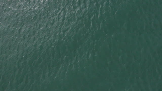 Aerial shot moving across calm sea water off the coast of southern England, UK.