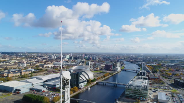 aerial shot moving around the glasgow science tower, with cityscape in the background - スコットランド グラスゴー点の映像素材/bロール