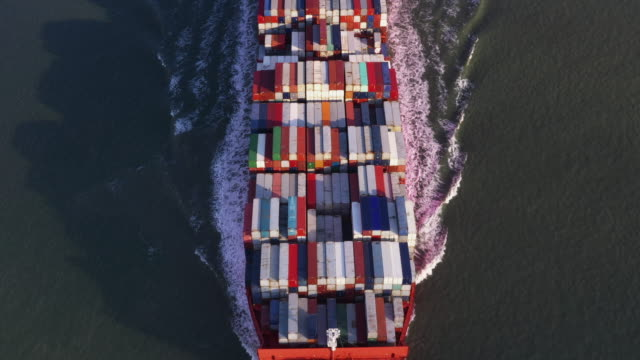 aerial shot moving back from a container ship on the move, netherlands - container ship stock videos & royalty-free footage
