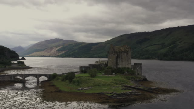 aerial shot moving back from eilean donan castle, scottish highlands, united kingdom - lakeshore stock videos & royalty-free footage