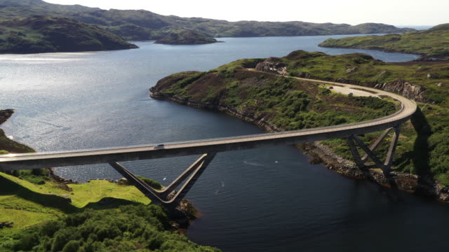 aerial shot moving backwards from a vehicle crossing kylesku bridge, scotland, united kingdom - ridge stock videos & royalty-free footage