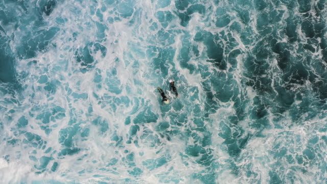 aerial shot moving down towards two surfers waiting in ocean swells, lanzarote, spain - seascape stock videos & royalty-free footage