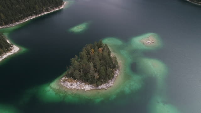 vídeos de stock, filmes e b-roll de aerial shot moving towards an island in lake eibsee, germany - montanha zugspitze